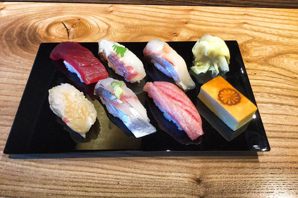 A selection of nigiri on a black plate at Wataru.