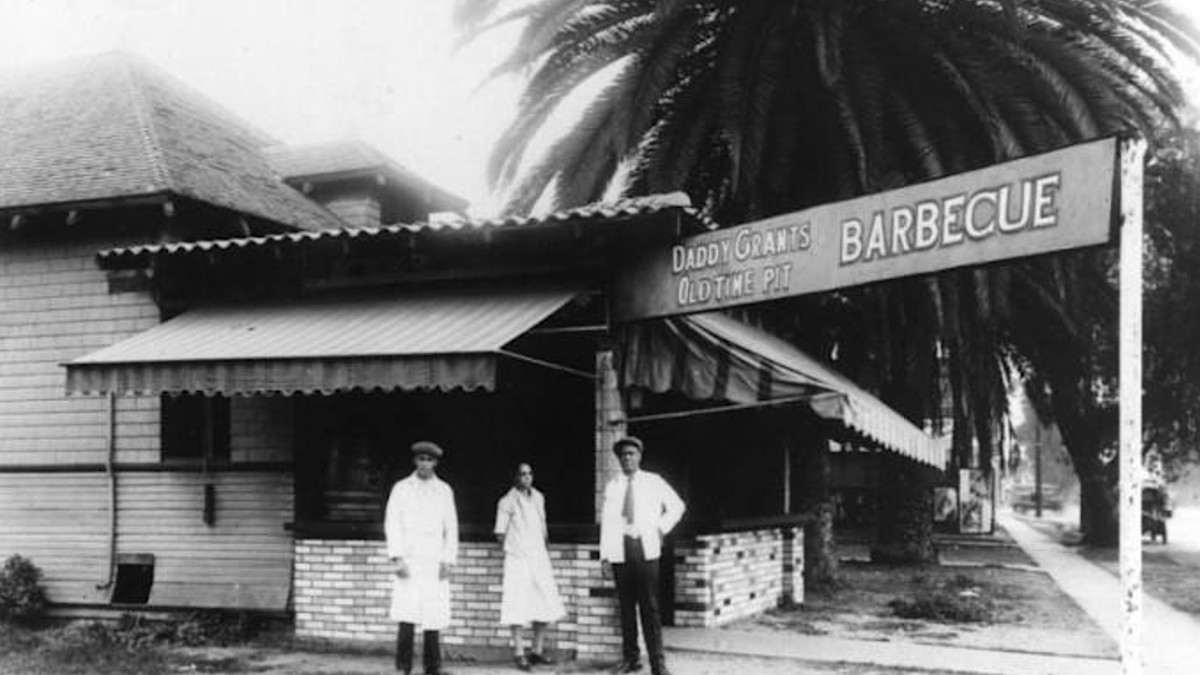 A black and white image of a barbecue restaurant with men standing in front.