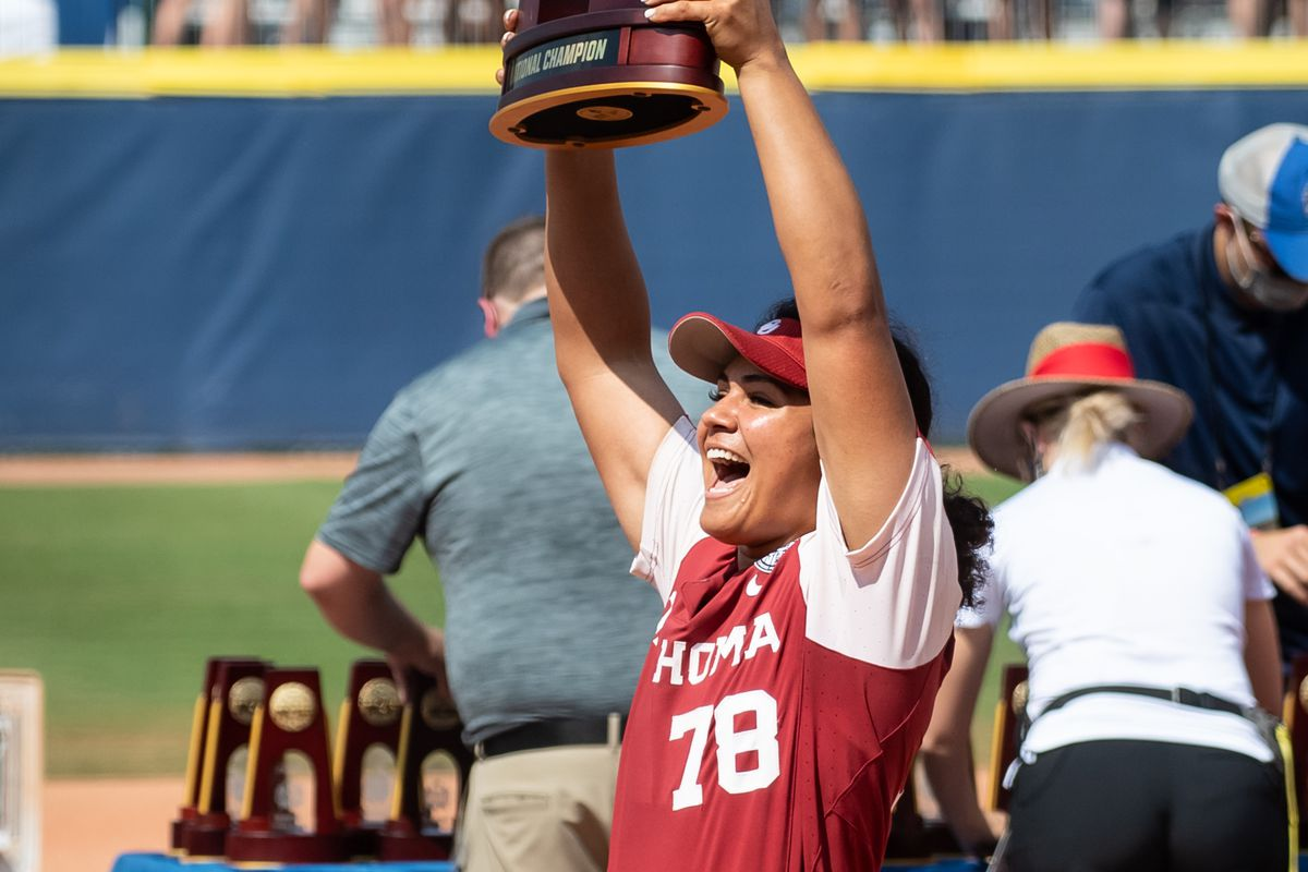 Jocelyn Alo of the Oklahoma Sooners yells while lifting the Womens College World Series trophy after she and her team won the tournament against Florida St.