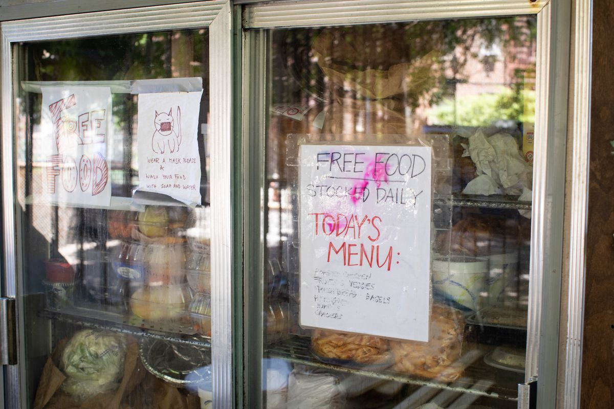"""The doors of an outdoor fridge with a sign that reads """"Free food stocked daily, Today's Menu."""""""