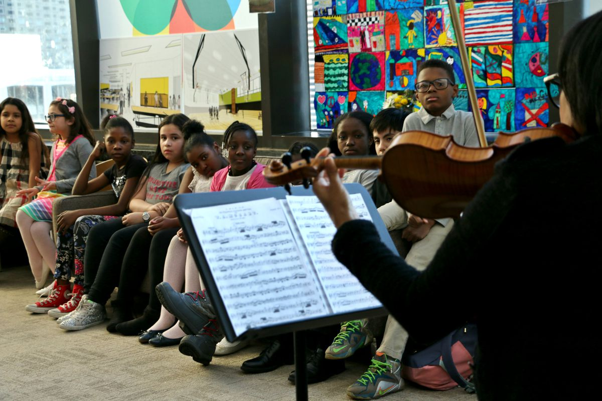 Students listened to their music teacher play violin at a P.S. 191 community event at Lincoln Center this spring. Fernando Taylor, a seventh-grade student who is the son of PTA President Charles Taylor, is seated far right. (Photo: Patrick Wall)