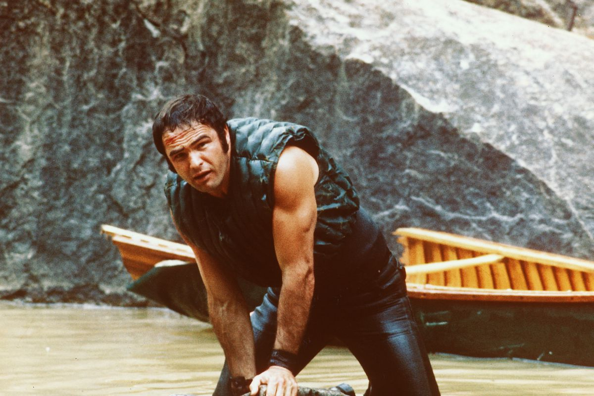 Burt Reynolds holding onto a rock in the water in 'Deliverance'