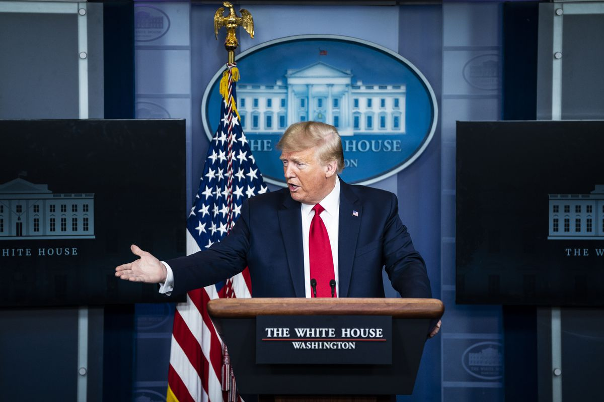 Trump, the seal of the White House behind him, along with a flag, gestures at a podium. He's wearing a dark navy suit, and a bright red tie.