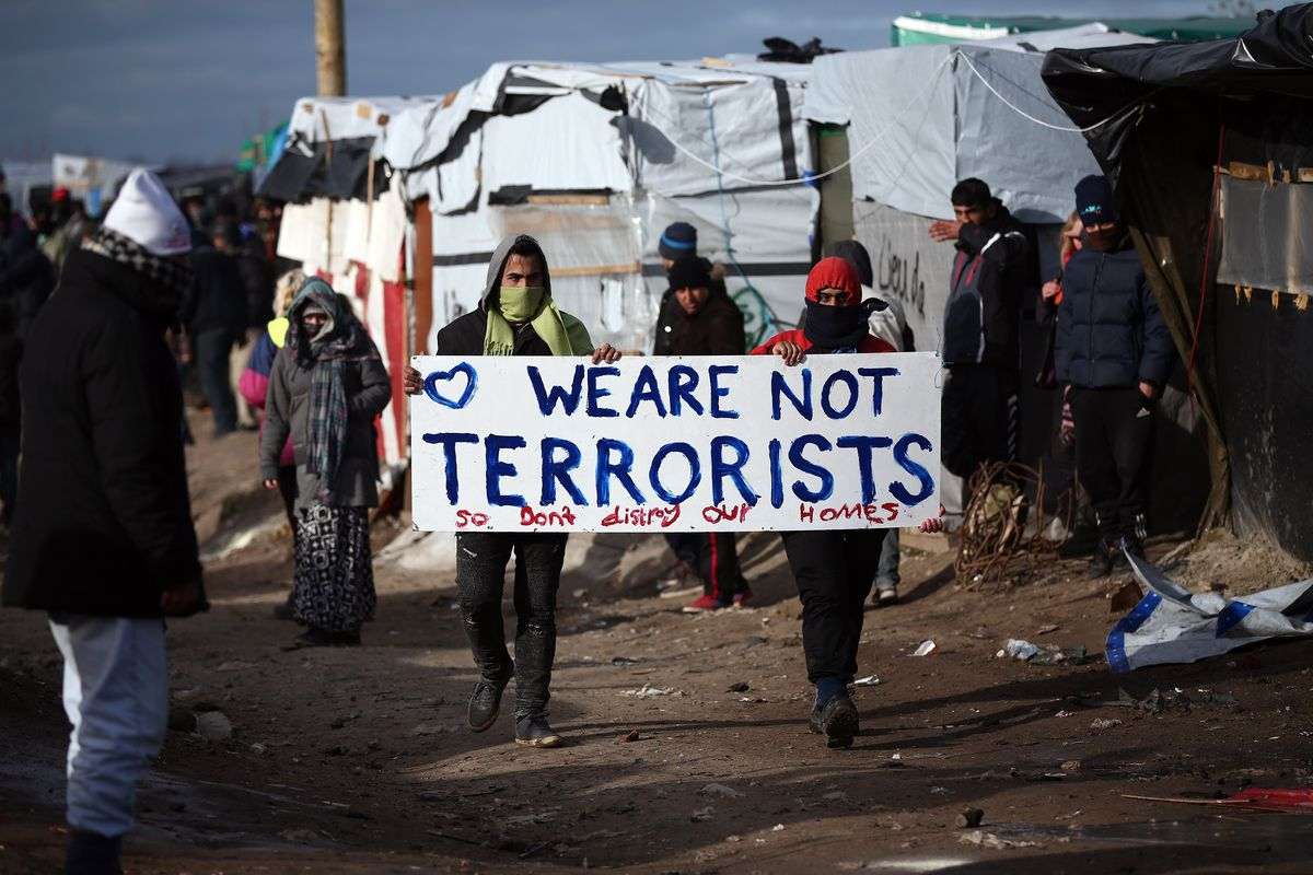 """camp residents carry a sign that says """"we are not terrorists so don't destroy our homes"""""""