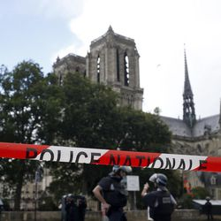 Police officers seal off the access to Notre Dame cathedral in Paris, France, Tuesday, June 6, 2017. Paris police say an unidentified assailant has attacked a police officer near the Notre Dame Cathedral, and the officer then shot and wounded the attacker.