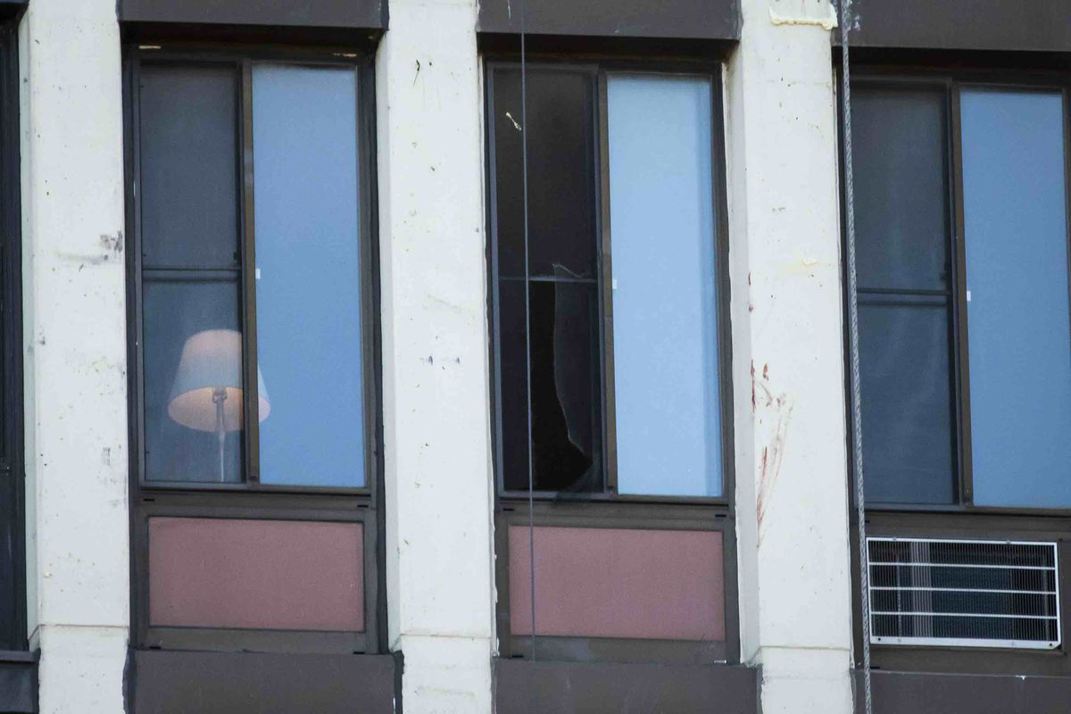 A broken screen hangs in an 11th-floor window of an apartment building in South Shore, where two boys were killed Thursday.