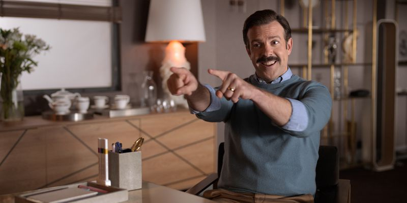 Ted Lasso, played by Jason Sudeikis, points excitedly at Rebecca (not pictured).