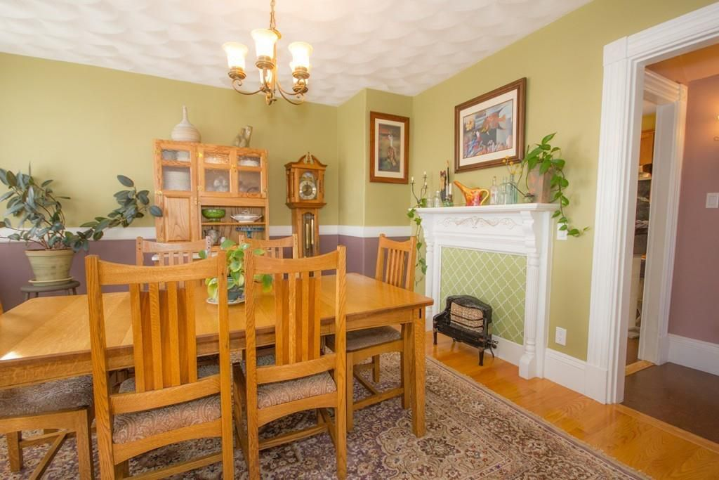 A bright dining room with a table and chairs and a fireplace that's been filled in.