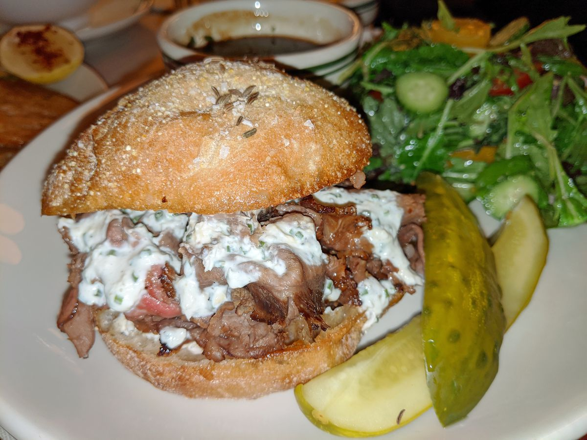 A beef sandwich on a round roll with white sauce coursing down the sides.