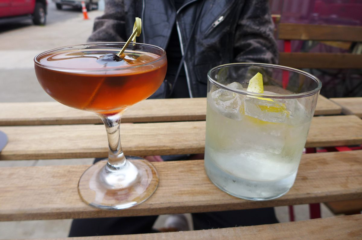 A pair of cocktail, one in a stemmed glass and dark orange, the other clear in a tumbler.