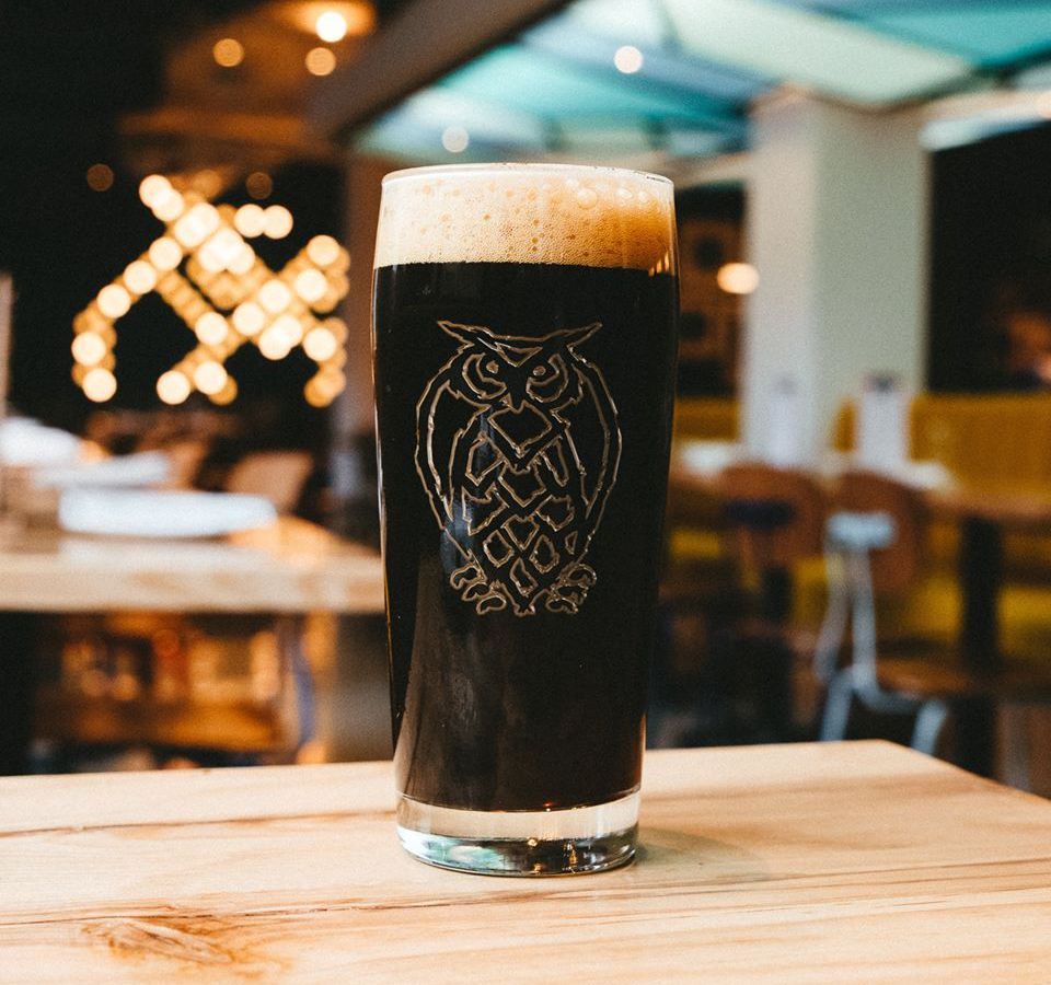 A dark beer in a glass with an owl logo sits on a light wooden table in a taproom. Angular turquoise details are visible on the ceiling, and a giant version of the owl logo is lit up on a wall in the background.
