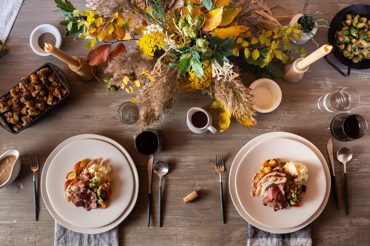 A Thanksgiving table with an autumn floral arrangement side dishes like cast iron stuffing and plates filled with neat piles of turkey and fixin's.