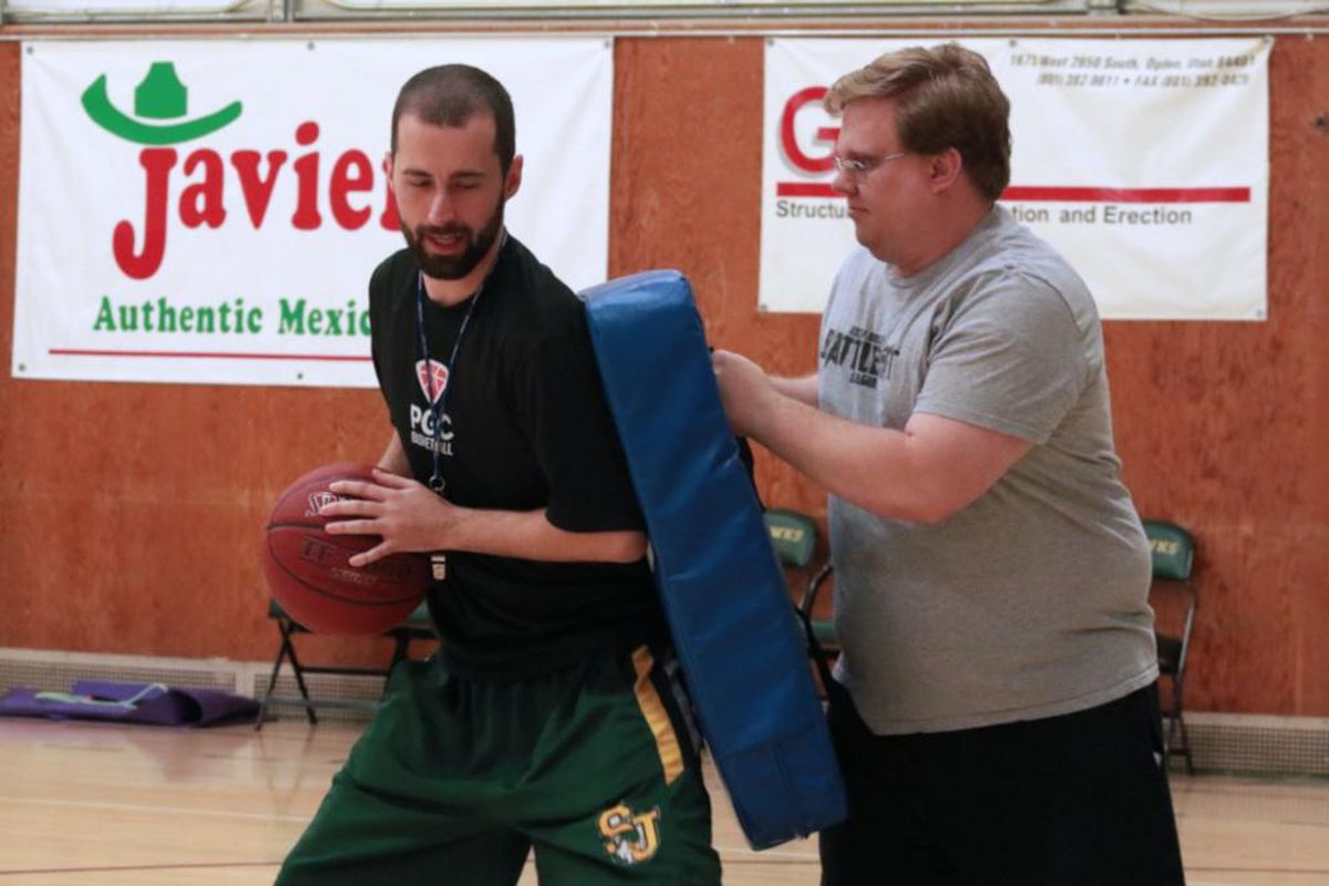 St. Joseph Catholic High School head coach Cameron Wood (left) demonstrates a basketball drill with sophomore coach Lafe Peavler (right) during a recent practice.
