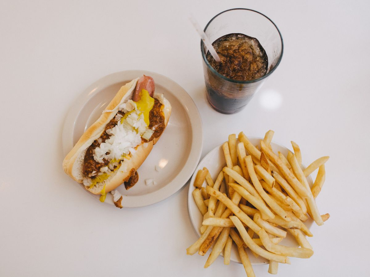 A coney dog with mustard, chili, and chopped white onions next to a plate of plain french fries and a cup of brown soda with ice and a straw.