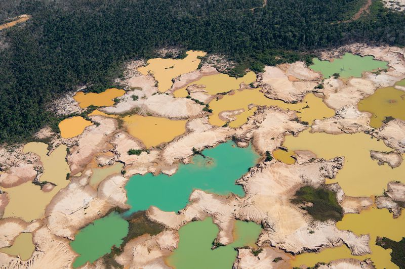An aerial view over a chemically deforested area of the Amazon jungle caused by illegal mining activities in the river basin of the Madre de Dios region in southeast Peru.