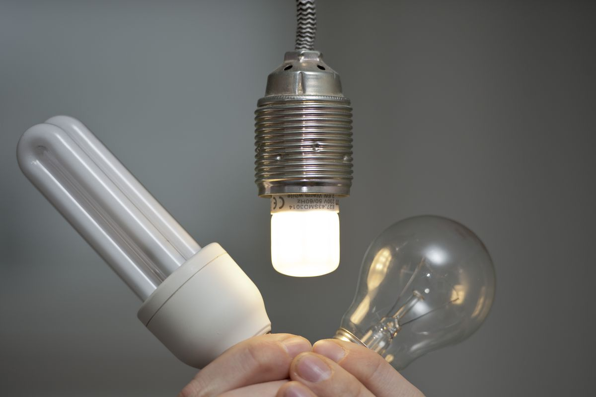 A glowing LED lamp in a lamp socket while an energy-saving light bulb and incandescent lights bulb is shown next to it.