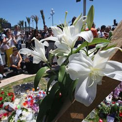 Floral tributes are laid out near the site of the truck attack in the French resort city of Nice, southern France, Friday, July 15, 2016. France has been stunned again after a large white truck killed many people after it mowed through a crowd of revellers gathered for a Bastille Day fireworks display in the Riviera city of Nice.