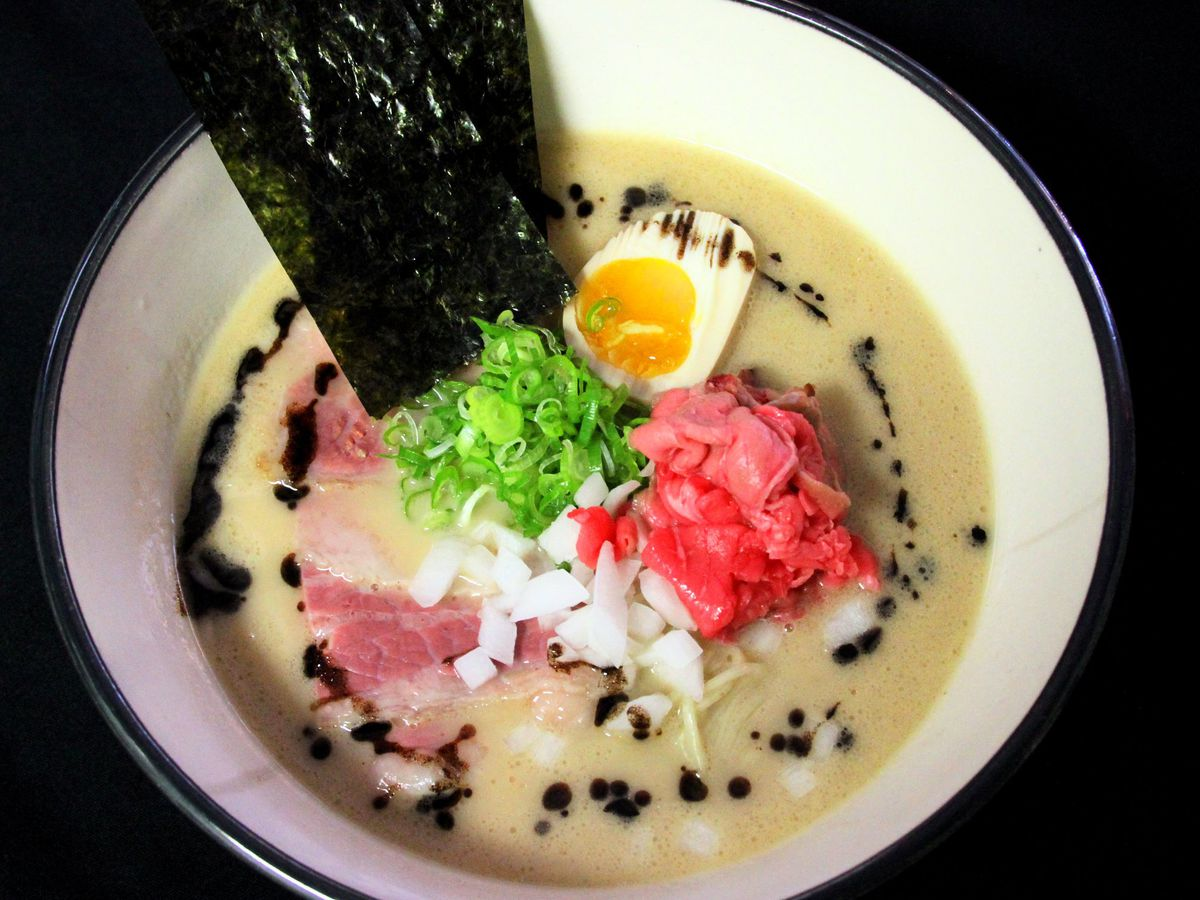 A creamy bowl fo beef ramen with a nori piece sticking out.