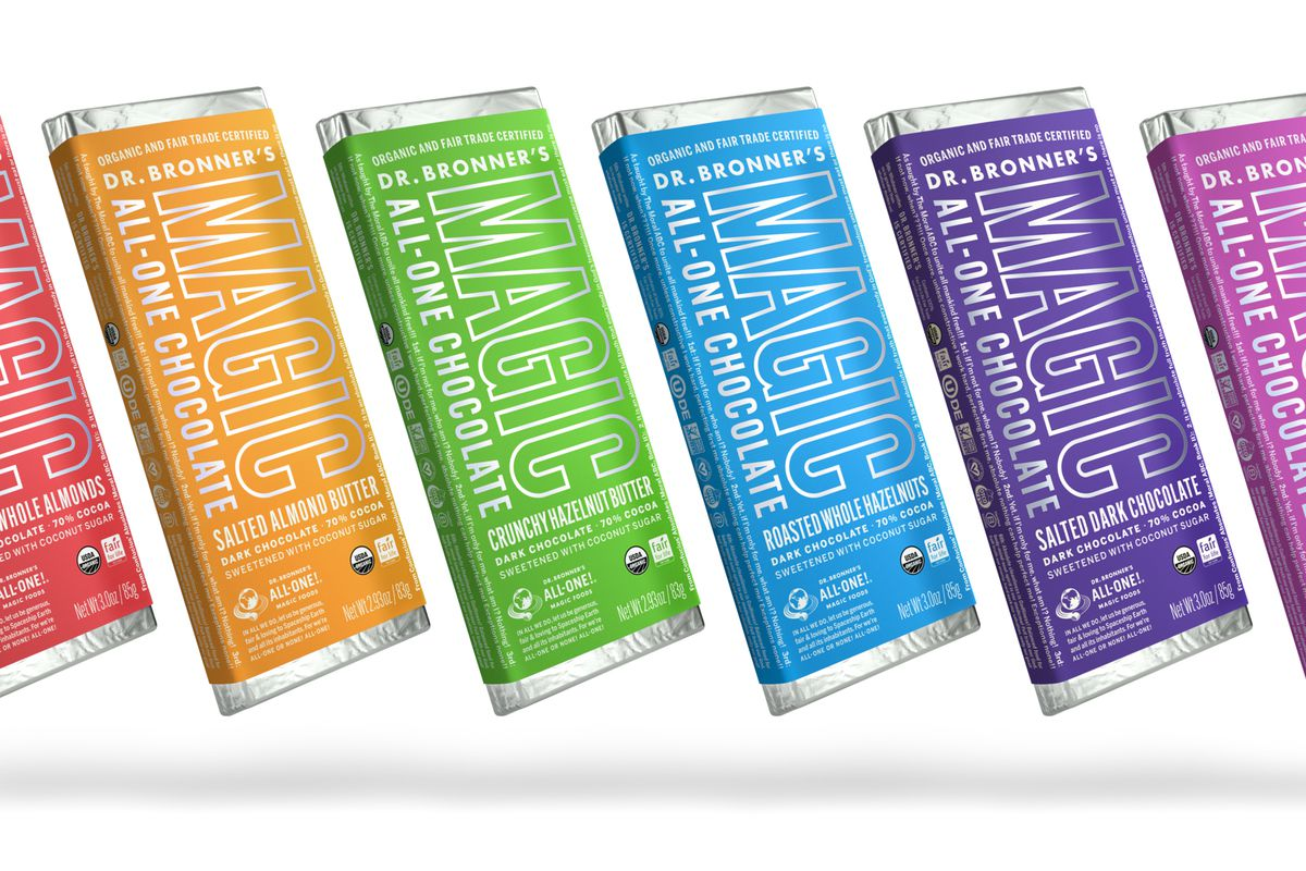 Four bars of Dr. Bronner's chocolate wrapped in a variety of brightly colored paper (yellow, green, blue, and purple), photographed against a white studio background.