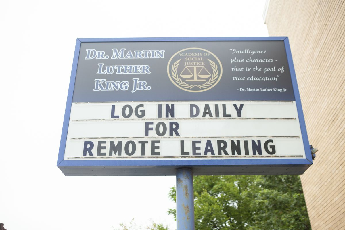 A sign outside Dr. Martin Luther King, Jr. Academy of Social Justice that reads: log in daily for remote learning.