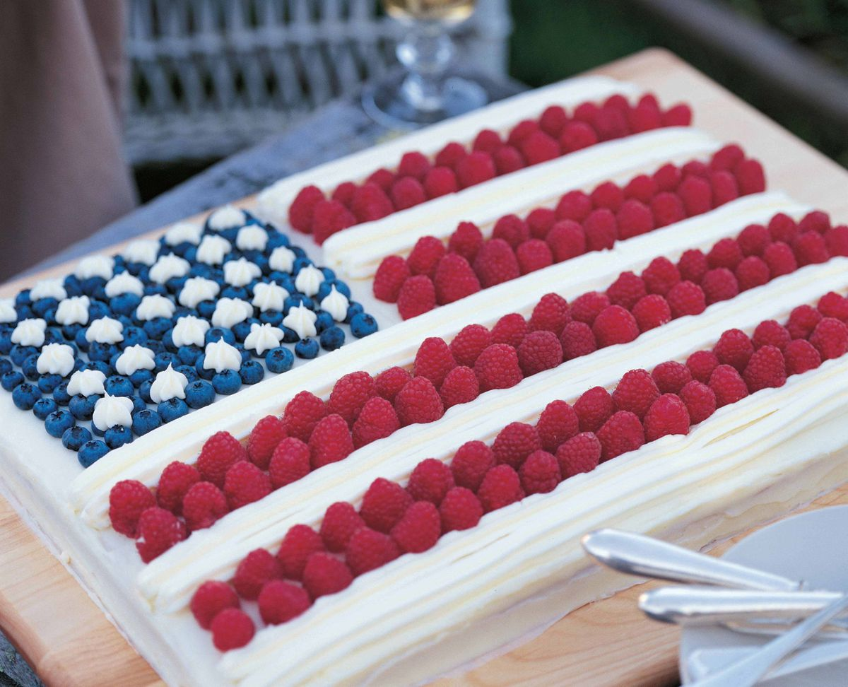 A cake with white frosting and dressed with blueberries and strawberries to mimic a flag design