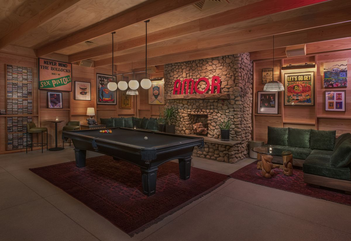 A pool table inside of a restaurant lounge area with fireplace beyond.