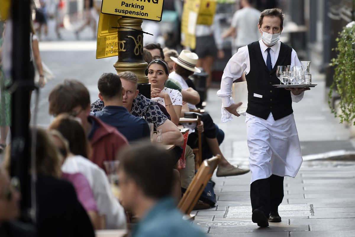 A masked waiter in white shirt and black jacket walks past a column of outdoor restaurant tables filled with diners in Soho, London