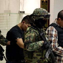 """The alleged leader of a faction of the hyper-violent Zetas cartel, Ivan Velazquez Caballero, known as """"El Taliban,"""" right,  is escorted to a media presentation at the Mexican Navy's Center for Advanced Naval Studies in Mexico City,Thursday, Sept. 27, 2012. Velazquez Caballero allegedly has been fighting a bloody internal battle with top Zetas' leader Miguel Angel Trevino Morales, and officials have said the split was behind a recent surge in massacres and shootouts, particularly in northern Mexico."""
