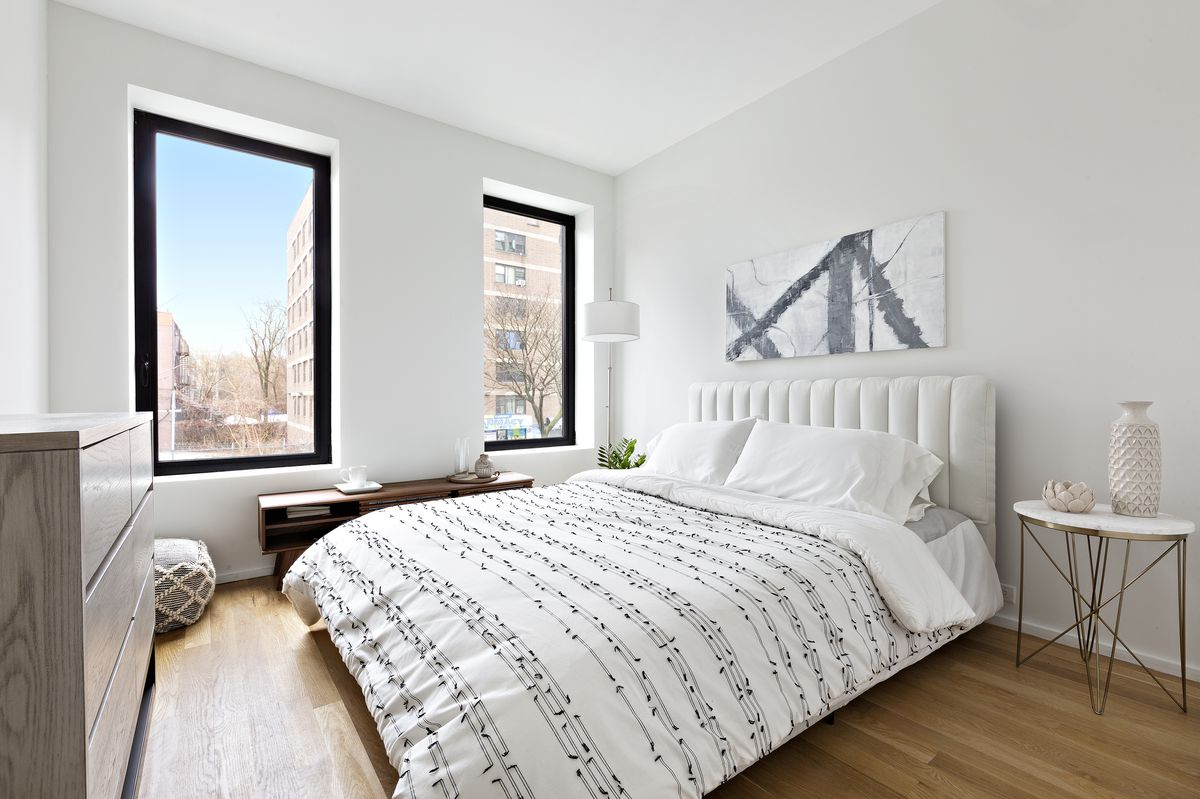 A bedroom with a large bed, two large windows, white walls, and hardwood floors.