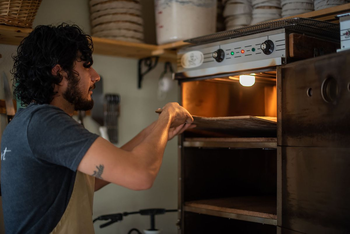 A baker drops dough into an oven with a light hanging above.
