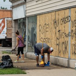 People clean up a boarded-up shop in Kenosha Tuesday afternoon, Aug. 25, 2020, after a night of unrest following the shooting of Jacob Blake by a police officer in Kenosha Sunday.
