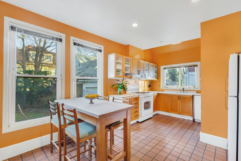A kitchen with a small table and four chairs, orange walls and cabinets, and three windows.