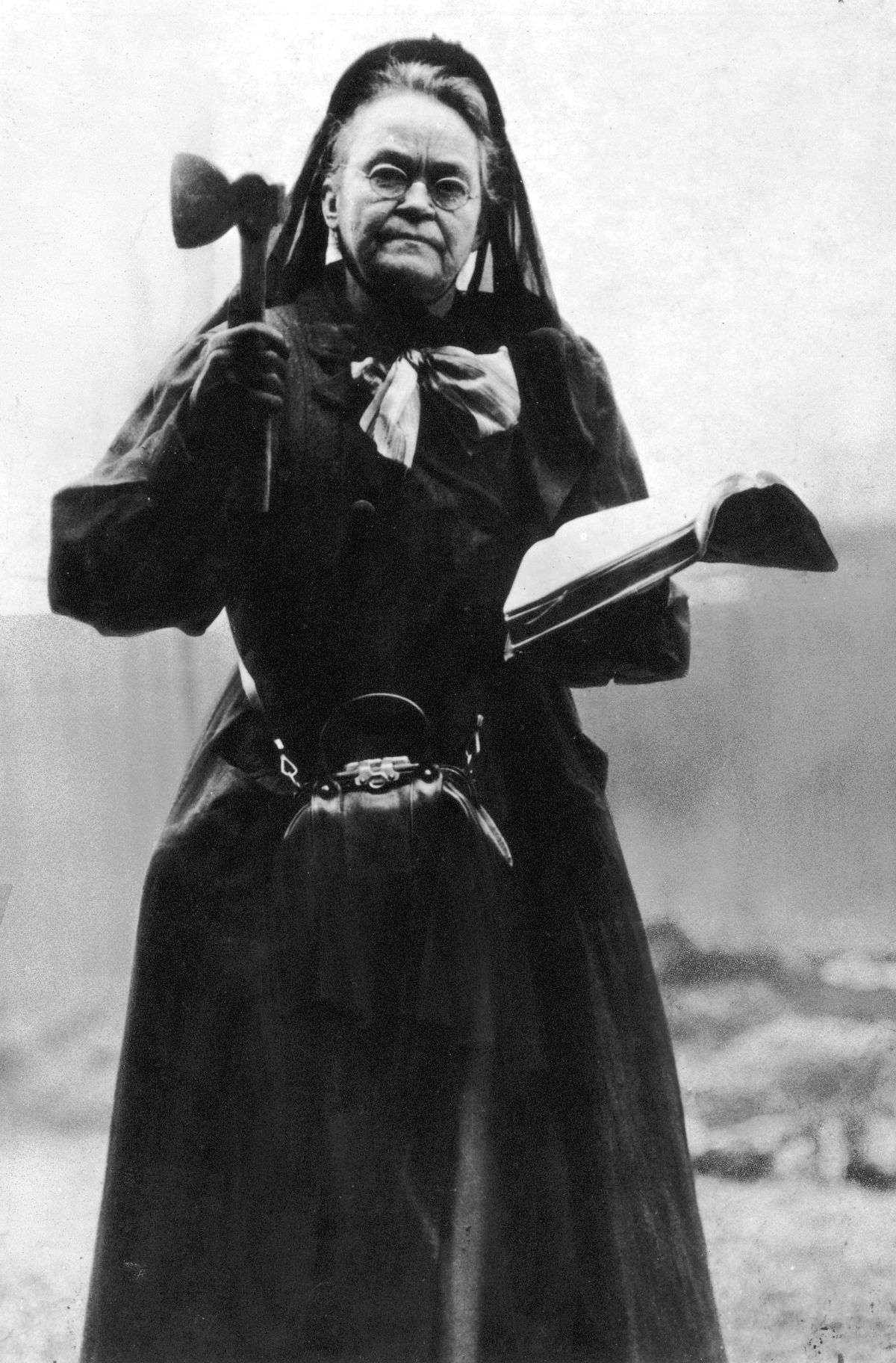 Portrait of American temperance reformer Carrie Nation (1846-1911) holding an axe and a bible. She wears a long dark dress, a dark veil, and a purse around her waist.