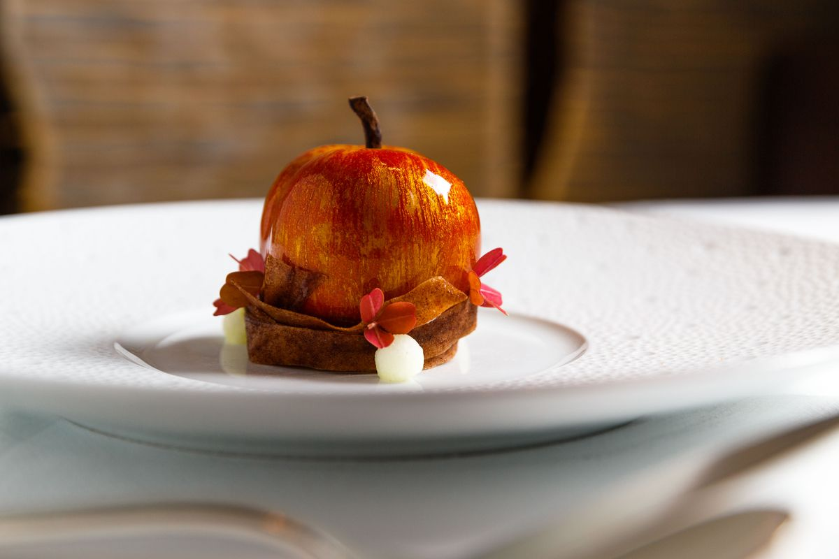 """Le Bernardin's """"apple"""" dessert sits on a white plate; the dish looks like real McIntosh but is really apple confit surrounded by glazed brown butter mousse"""
