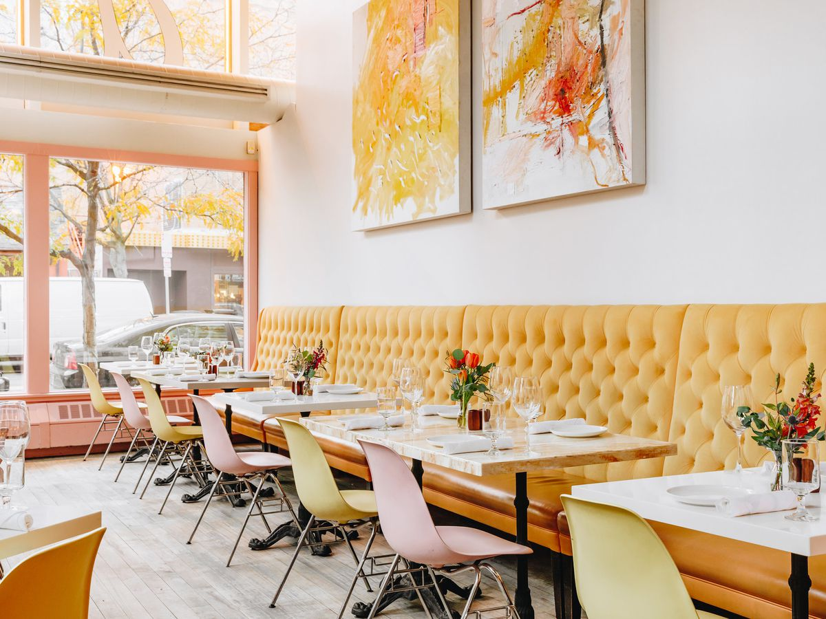 the dining room at sava's has lots of light from big windows and a line of yellow banquette seats with white marble tables and red flowers on top. The chairs are pink and green bucket seats.