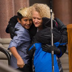 Newly inaugurated Salt Lake Mayor Jackie Biskupski, center, hugs her fiancÉe's son, Jack Iverson, left, and her own son, Archie, following her remarks outside the City-County Building on Monday, Jan. 4, 2016.