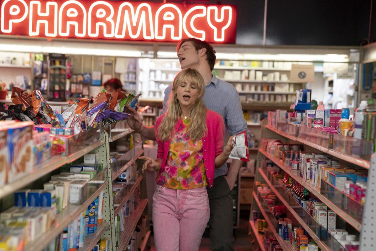 Two young white people stand in the center of an aisle in a pharmacy, singing.