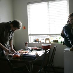 Kelsie Mason, right, watches as Eric Richardson, left, prepares hobo dinners at a her apartment before he heads up to the tent for the night.