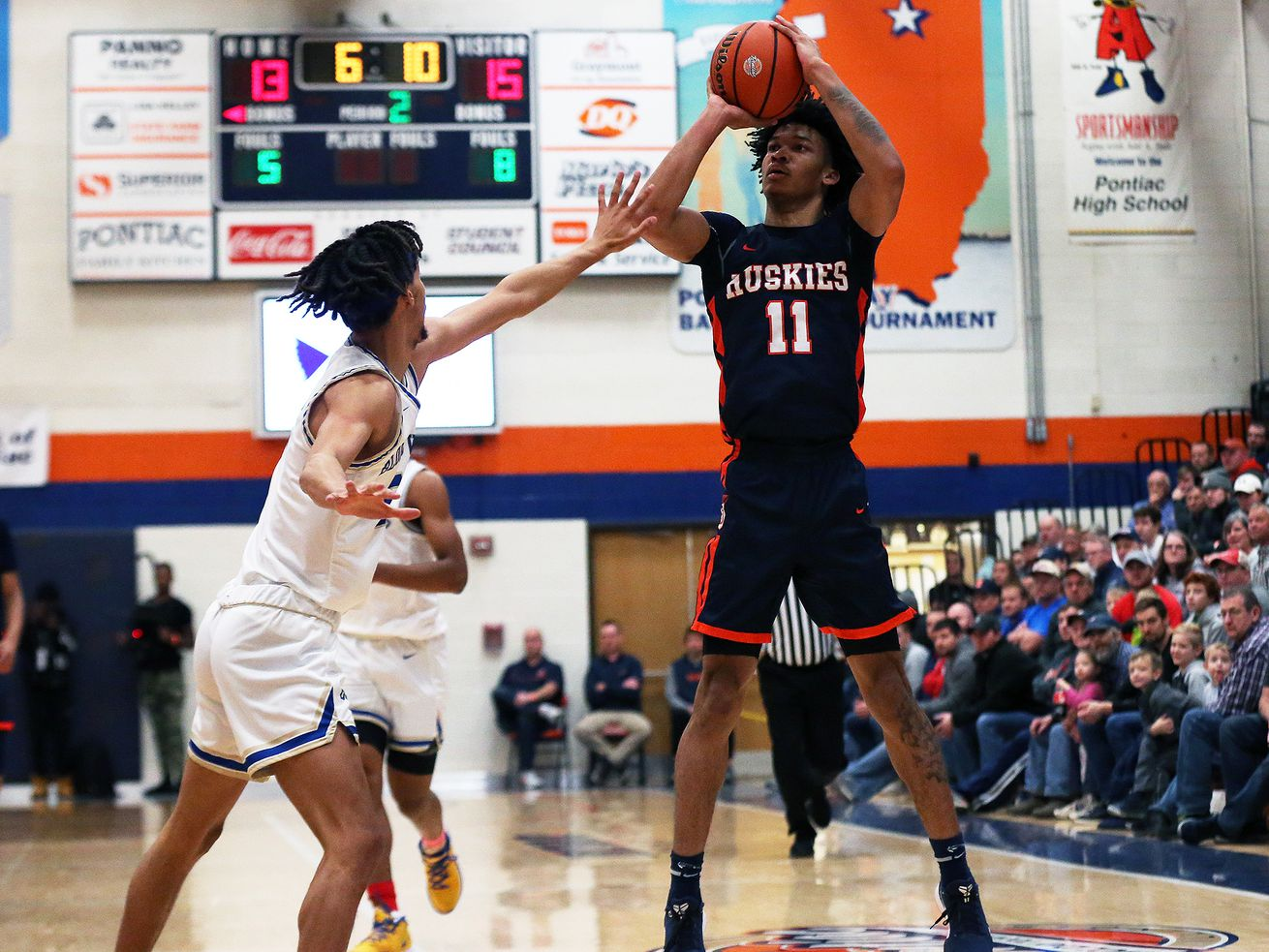 Isaiah Barnes (11), playing for Oak Park last season, shoots a three against Bloom. He is expected to sign with Michigan later this week.