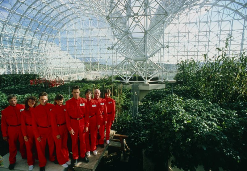 A group of people in red jumpsuits in a glass dome.
