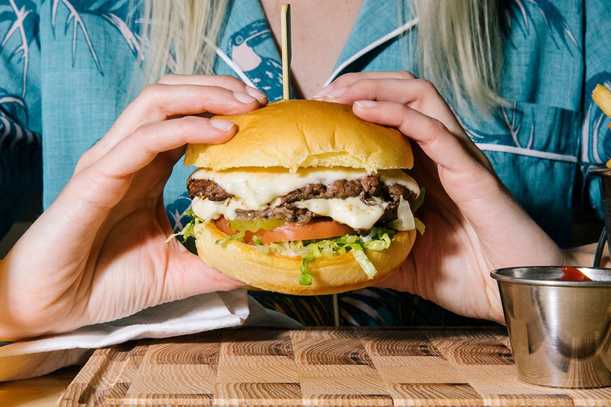 A person in a blue shirt holding up a burger with patties, cheese, tomatoes, and lettuce over a wooden table