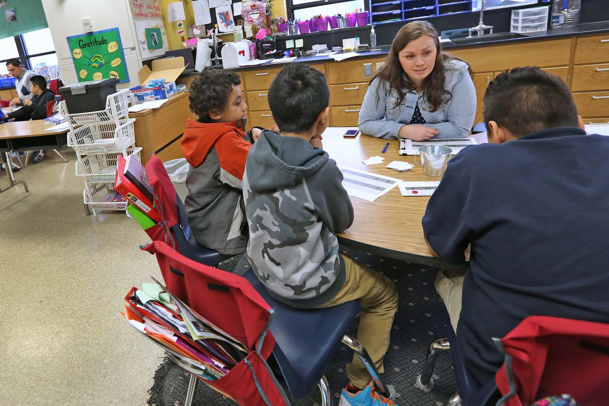 Fourth grade lead teacher Kate Skeens, right center, works with students at Enlace Academy, Tuesday, April 14.  Much of the instruction at the school takes place in small groups. The Mind Trust selected Enlace's leaders to run innovation network schools.