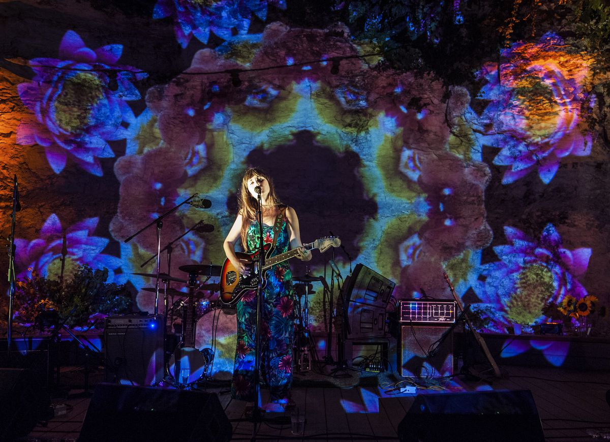 Jess Williamson on stage at Cheer Up Charlies, the stage has a psychedelic floral pattern being projected on it.