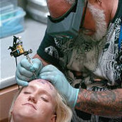 """Don Brouse tattoos """"Goldenpalace.com"""" on Kari Smith's forehead. Brouse and his staff at ASI Tattoo spent nearly seven hours trying to talk Smith out of it."""
