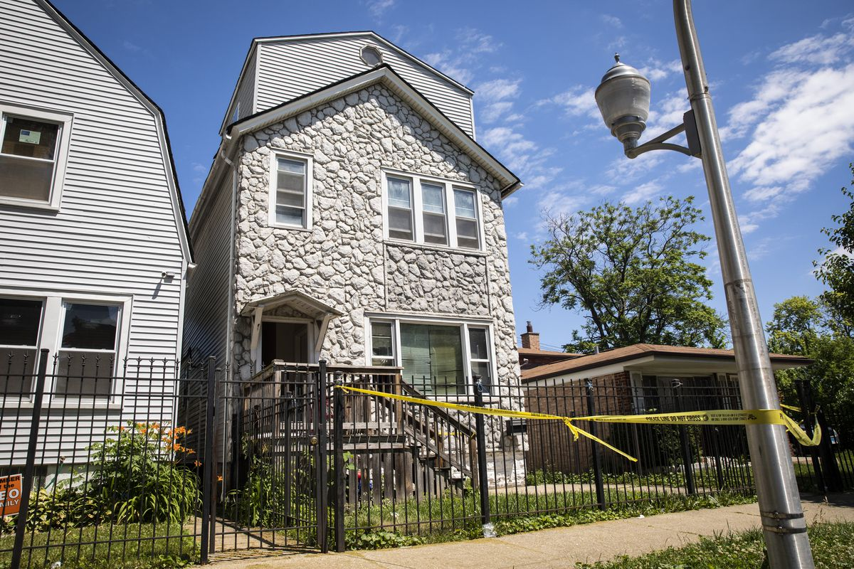 Chicago police keep watch Tuesday afternoon and crime scene tape hangs outside a house in the 6200 block of South Morgan, where eight people were shot, four fatally, inside the Englewood building,
