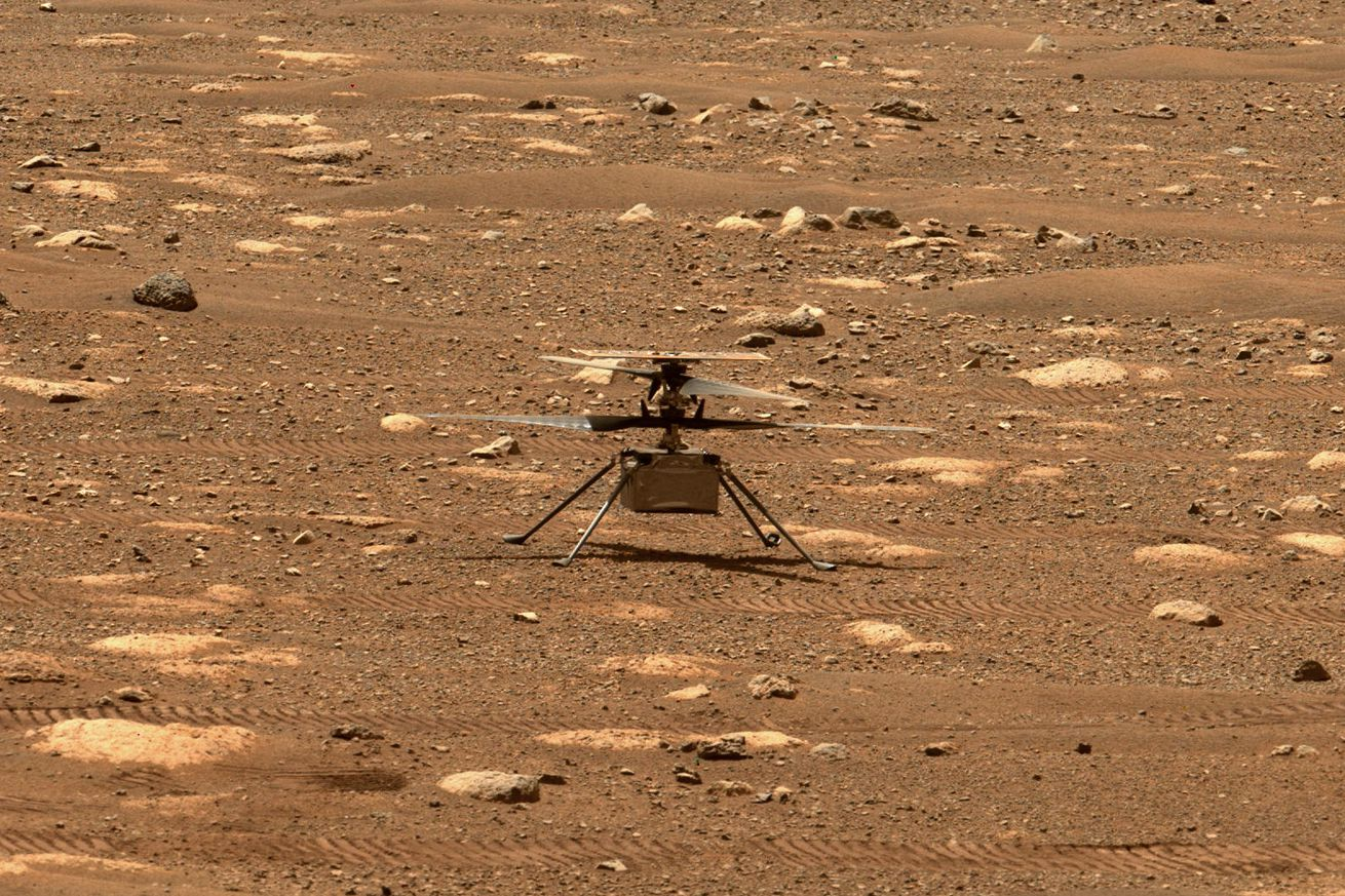 A tiny helicopter standing on four skinny legs on the dusty red Martian surface.