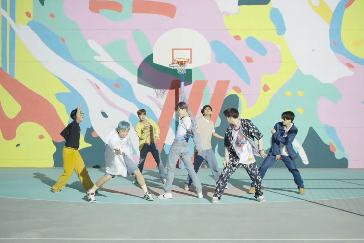 The members of BTS dance and pose in front of a pastel-colored painted wall