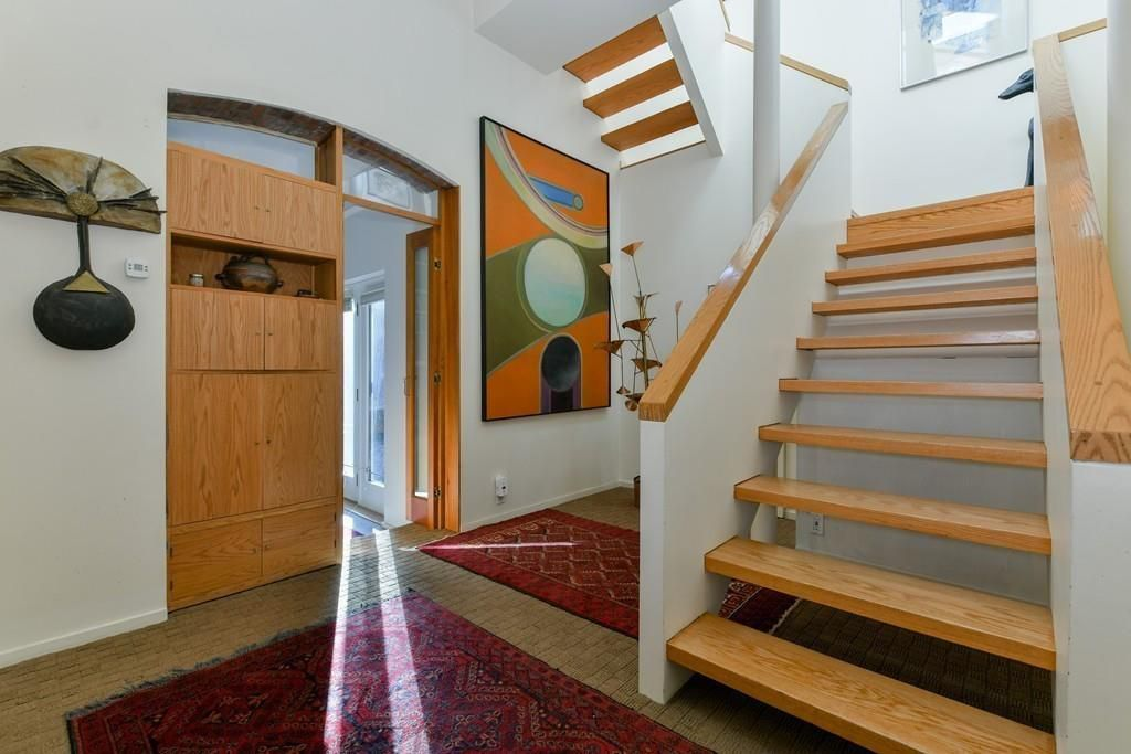 An entry foyer with a wide staircase leading right up from it.