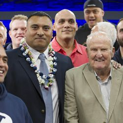 Former players and former head coach LaVell Edwards pose for photos with new head coach Kalani Sitake, following a press conference in Provo Monday, Dec. 21, 2015.