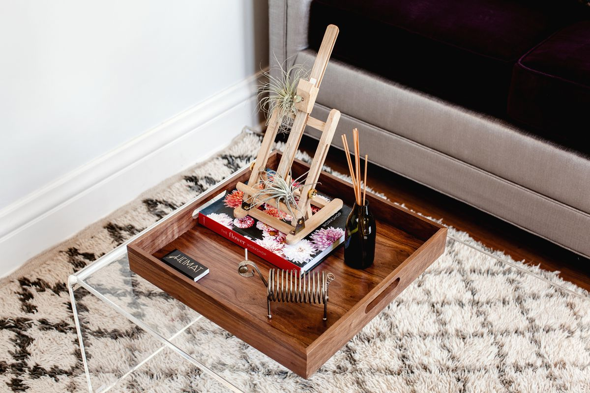 A clear coffee table is made from acrylic. It holds a tray that frames a scene of design books, a plant laden easel, and trinkets. A patterned rug can be seen beneath.
